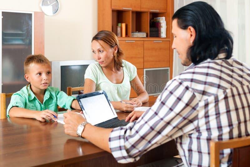 Förälder- och tonåringson som talar med anställd arkivbilder
