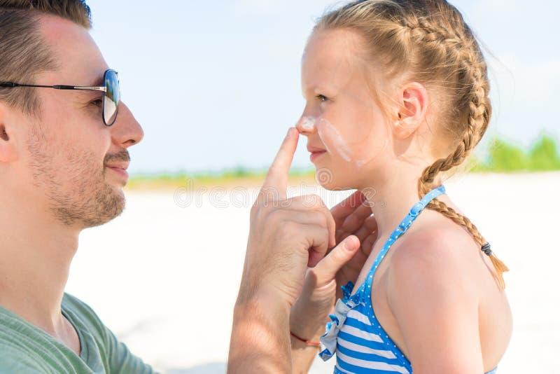 Förälder som applicerar solkräm till ungenäsan Stående av den gulliga flickan i suncream arkivbild