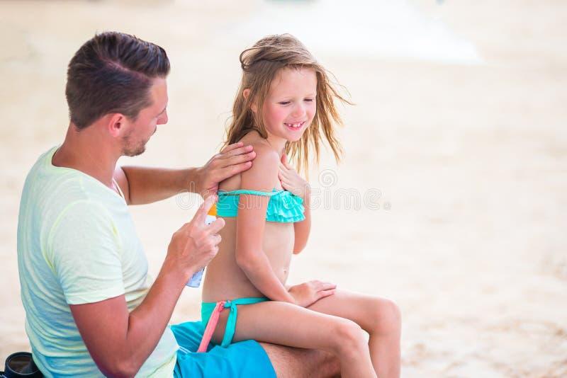 Förälder som applicerar solkräm till ungenäsan Stående av lttleflickan i suncream arkivfoto