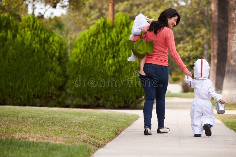 Förälder som tar barn trick eller behandlar på allhelgonaaftonen arkivfoton