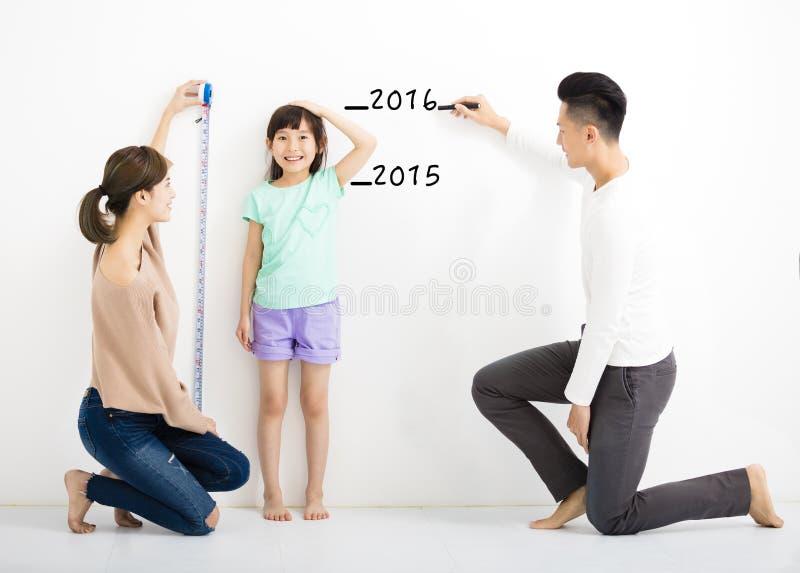 föräldern mäter tillväxten av dottern royaltyfri fotografi