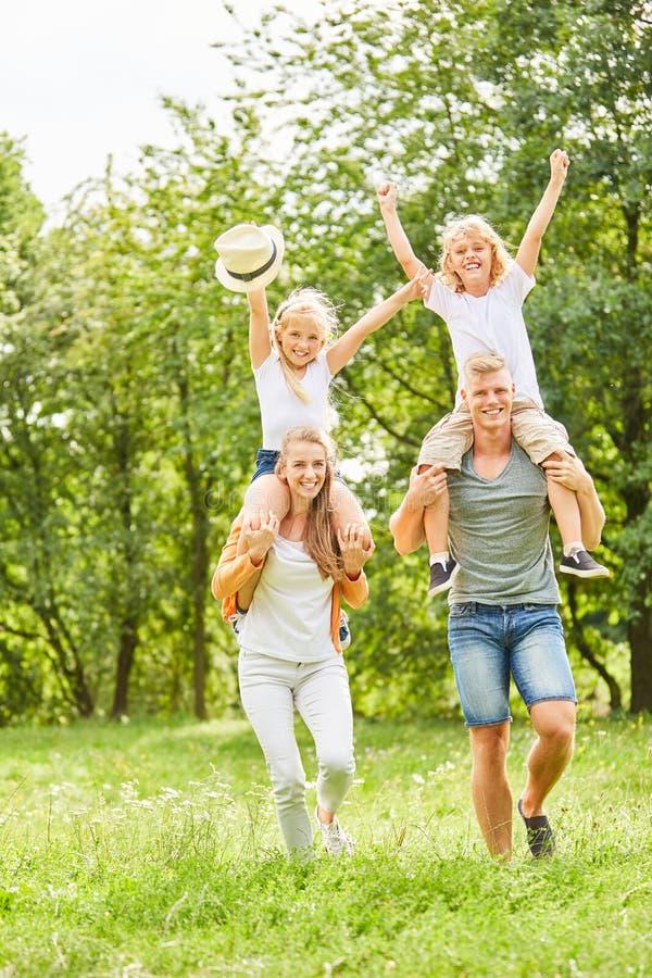 Föräldrar bär gladlynta barn på ryggen royaltyfri fotografi
