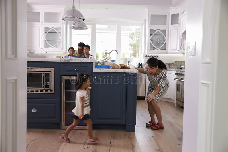 Föräldrar förbereder mat som barnlek i kök royaltyfria bilder