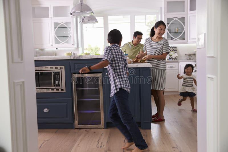 Föräldrar förbereder mat som barnlek i kök arkivbild