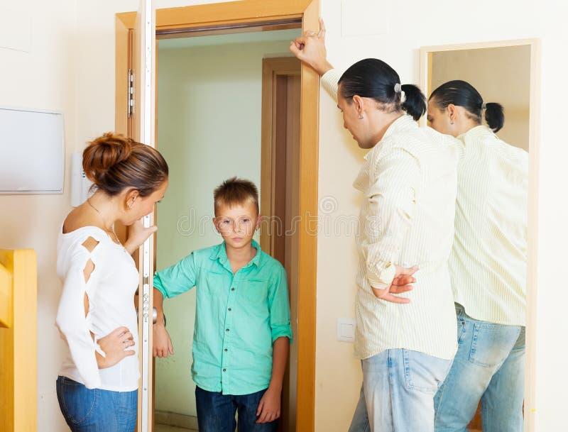 Föräldrar grälar på sonen, som gick tillbaka senare hem royaltyfri bild