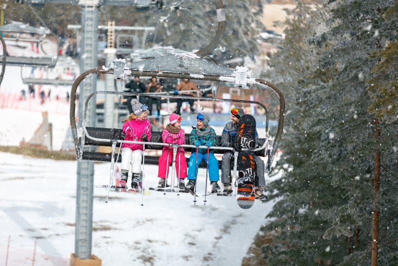 Föräldrar med barn klättrar upp på skidaterrängen med stollif royaltyfria bilder
