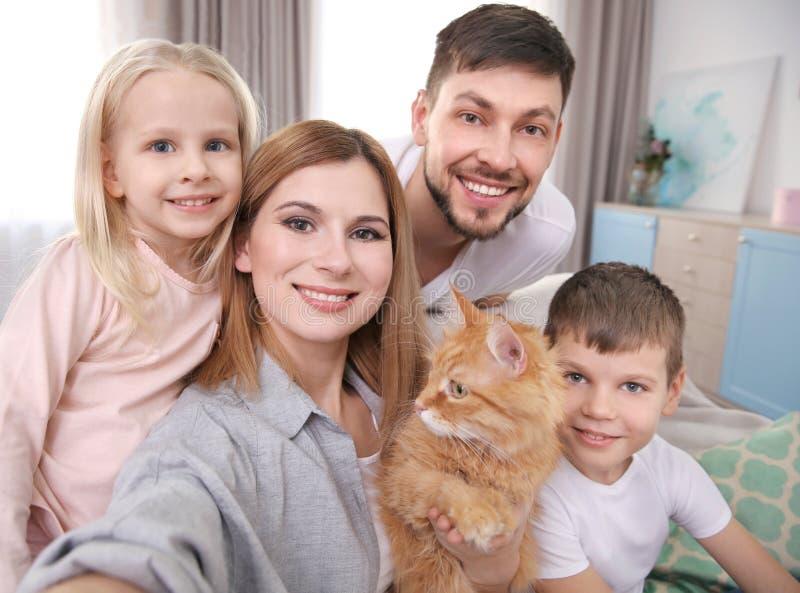 Föräldrar med barn och katten som tar selfie arkivfoto