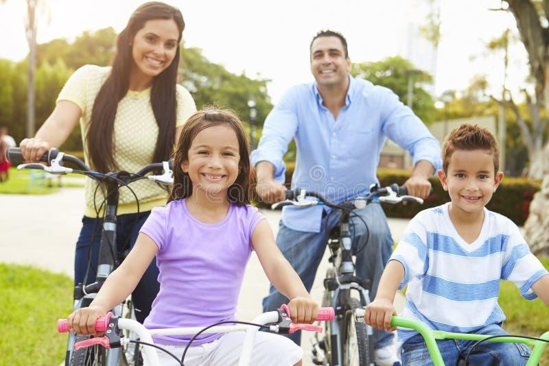 Föräldrar med barn som rider cyklar parkerar in royaltyfri bild