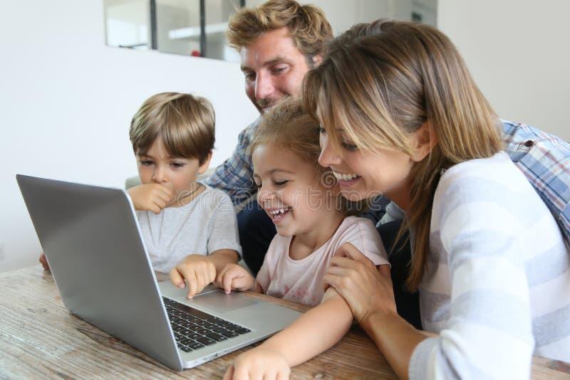 Föräldrar med barn som spelar på bärbara datorn royaltyfri bild