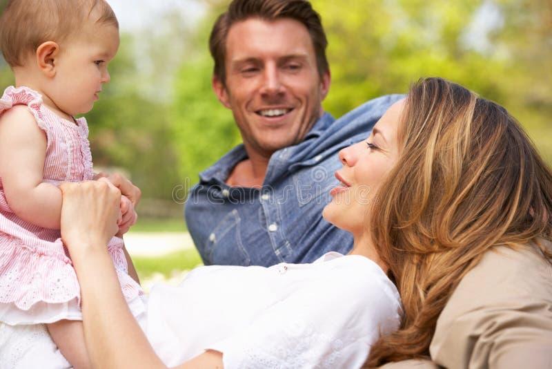 Föräldrar med behandla som ett barn flickan som sitter i fält arkivbild