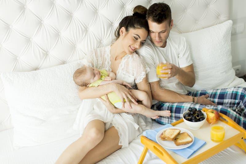 Föräldrar med behandla som ett barn ha frukosten i säng fotografering för bildbyråer