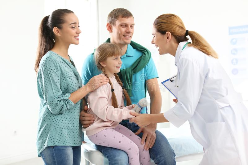 Föräldrar med den lilla dottern som besöker barns doktor arkivfoton