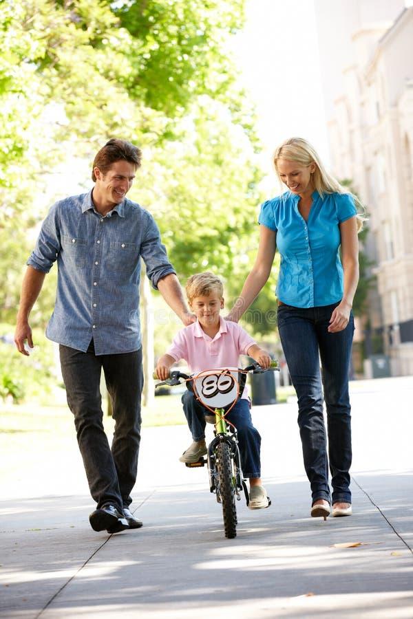 Föräldrar med den unga pojken på cykeln fotografering för bildbyråer
