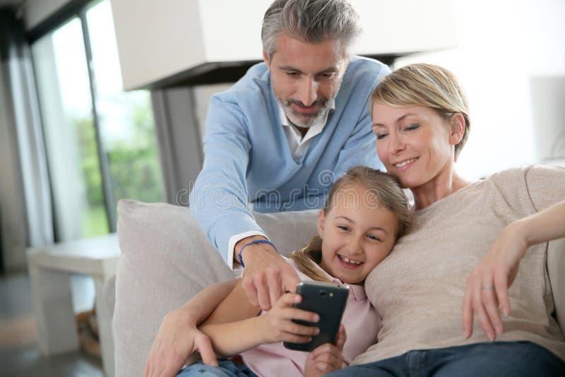 Föräldrar med deras dotter som spelar på minnestavlan fotografering för bildbyråer