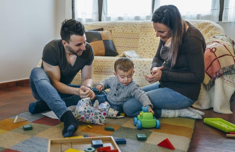 Föräldrar med deras lilla son som öppnar en gåva royaltyfria foton