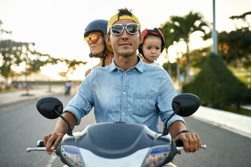 F?r?ldrar med deras ridningmotorcykel f?r liten unge p? den soliga stadsgatan royaltyfri fotografi