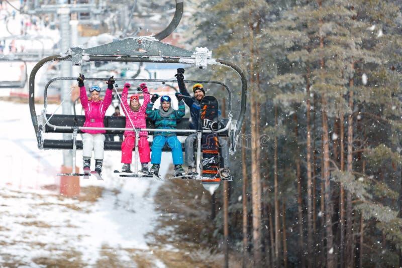 Föräldrar med det manliga och kvinnliga barnet i stolelevator klättrar på skidar upp royaltyfri bild