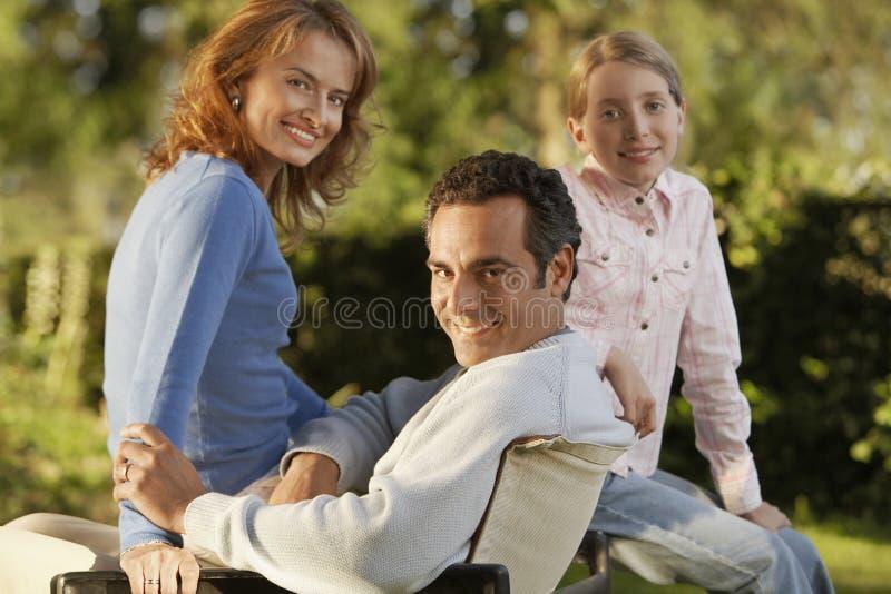 Föräldrar med dottern i trädgård royaltyfria foton