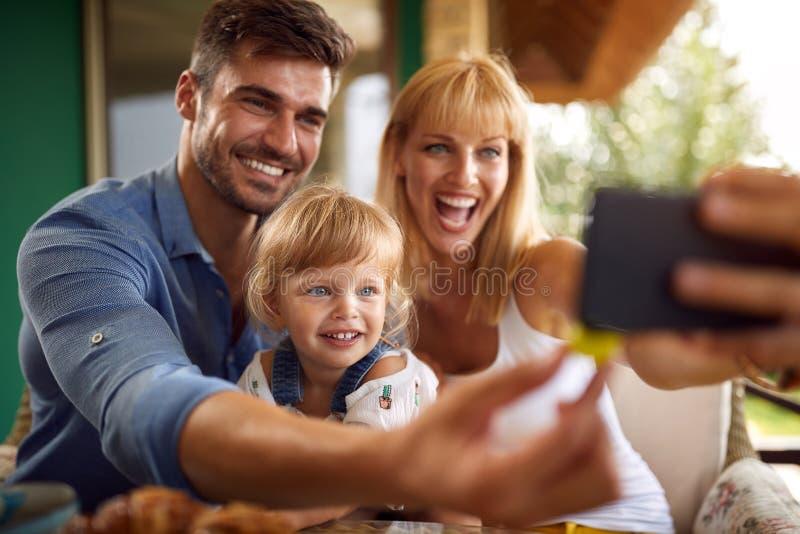 Föräldrar med dottern som tar selfie royaltyfria bilder