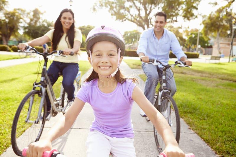 Föräldrar med dotterridning cyklar parkerar in fotografering för bildbyråer