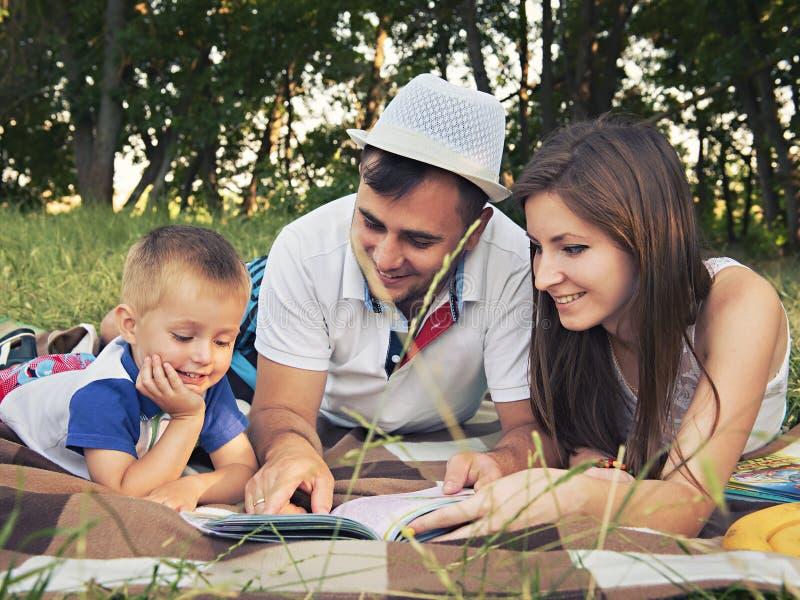 Föräldrar med ett barn som utomhus läser en bok fotografering för bildbyråer
