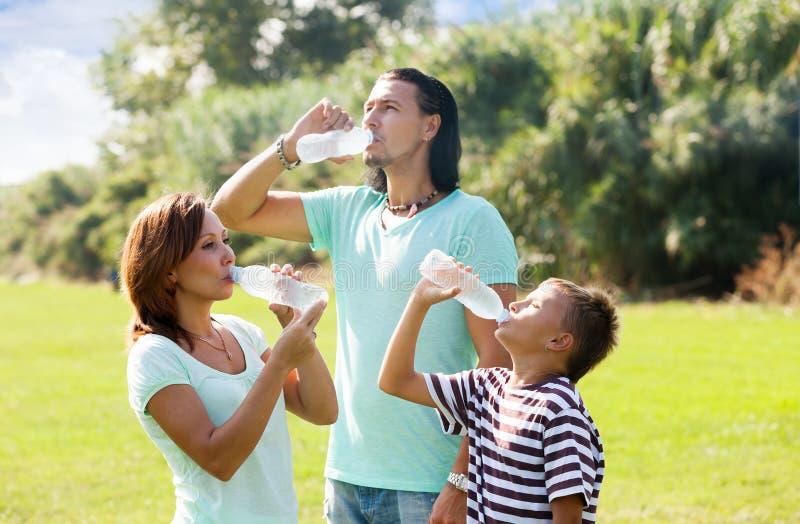 Föräldrar med tonåringen som dricker rent vatten royaltyfri fotografi