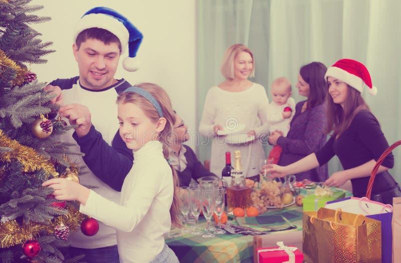 Föräldrar med ungar som förbereder sig för jul arkivbild