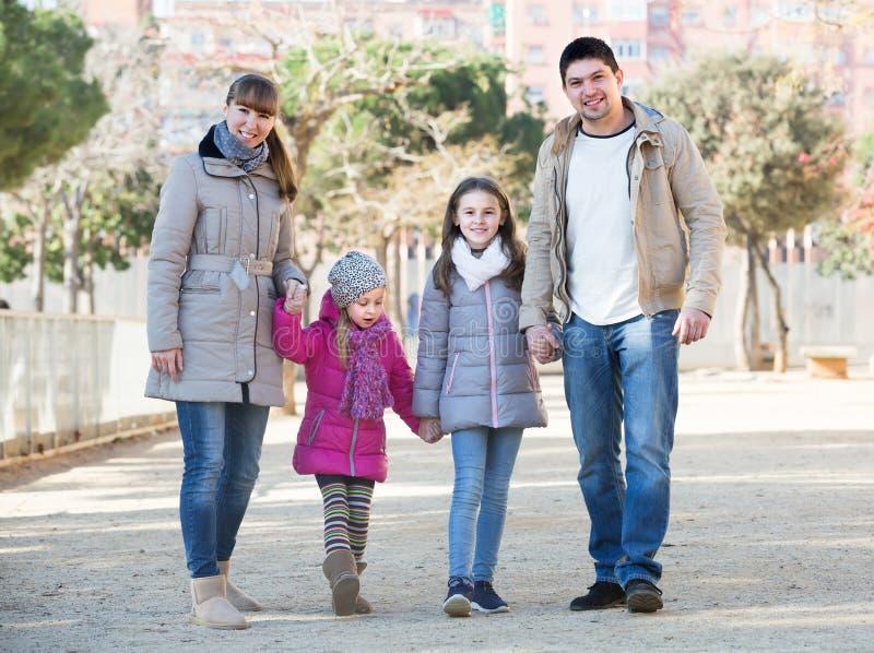 Föräldrar med ungar som går i gatan arkivfoto
