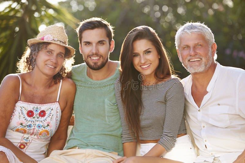 Föräldrar med vuxna avkommor som tillsammans kopplar av i trädgård royaltyfri fotografi