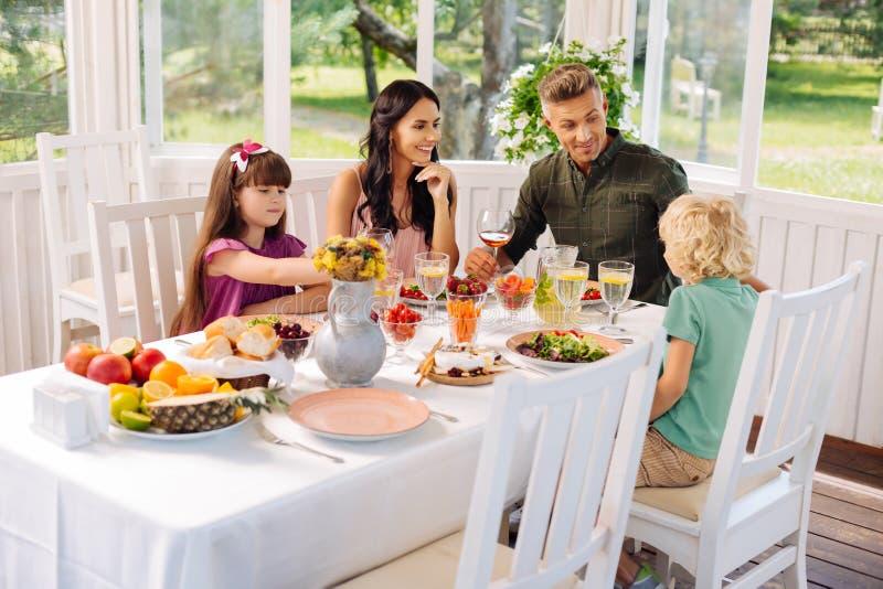 Föräldrar och barn som äter sallader, medan ha lunchyttersidan fotografering för bildbyråer