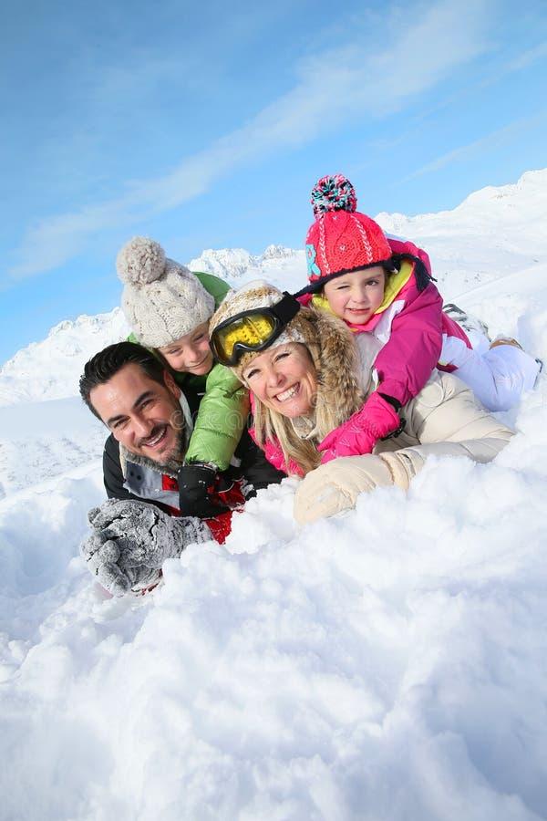 Föräldrar och barn som ligger i snö royaltyfria foton
