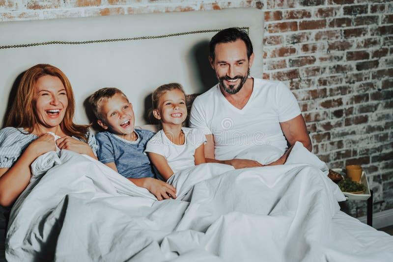 Föräldrar och barn som tillsammans håller ögonen på rolig film arkivfoto
