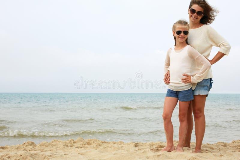 Föräldrar och barn vilar på kusten arkivbild