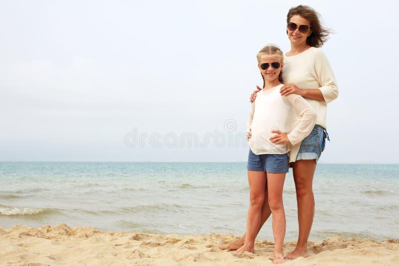 Föräldrar och barn vilar på kusten royaltyfria foton