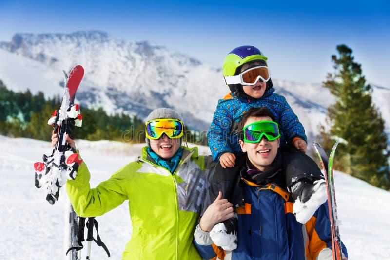 Föräldrar och barnet på farsans skuldror skidar in maskeringar royaltyfri foto