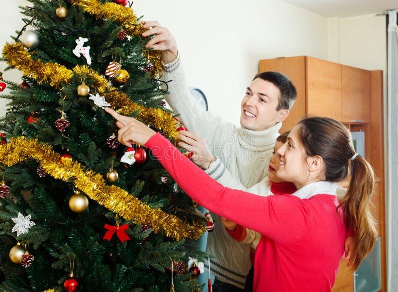 Föräldrar och behandla som ett barn dekorera julgranen arkivfoto