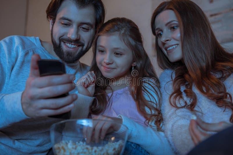 föräldrar och dotter som ser smartphonen fotografering för bildbyråer