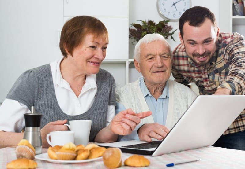 Föräldrar och hållande ögonen på foto för son royaltyfri fotografi