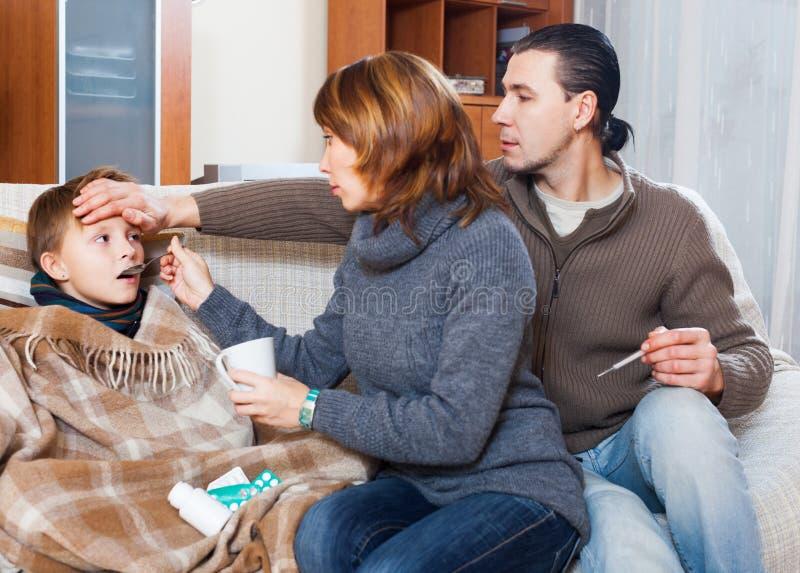 Föräldrar och son med termometern royaltyfri bild
