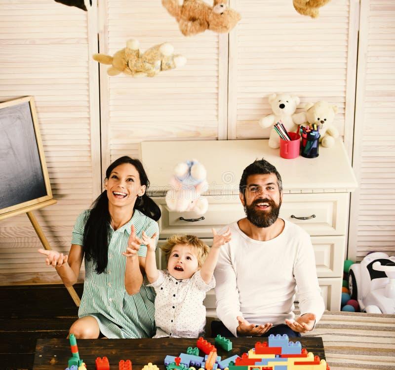 Föräldrar och sonen med lyckliga framsidor spelar med mjuka leksaker royaltyfria foton