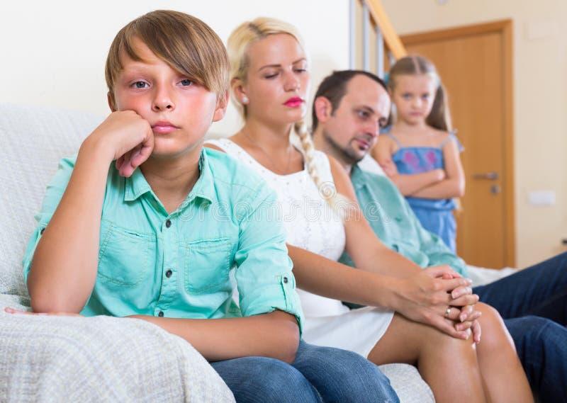 Föräldrar och två ungar i konflikt hemma royaltyfri foto