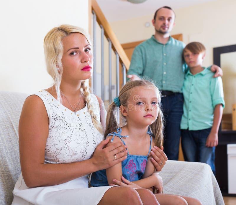 Föräldrar och två ungar i konflikt hemma fotografering för bildbyråer