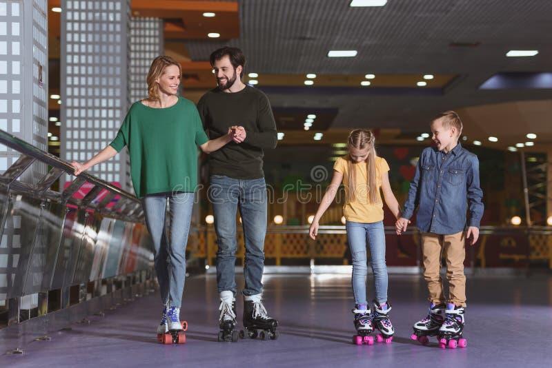föräldrar och ungar som åker skridskor på rullen royaltyfria foton