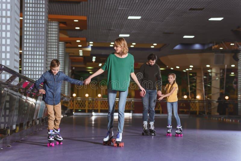 föräldrar och ungar som åker skridskor på rullen arkivfoto