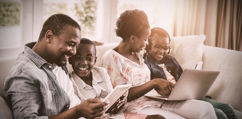 Föräldrar och ungar som använder bärbara datorn och den digitala minnestavlan på soffan royaltyfria foton