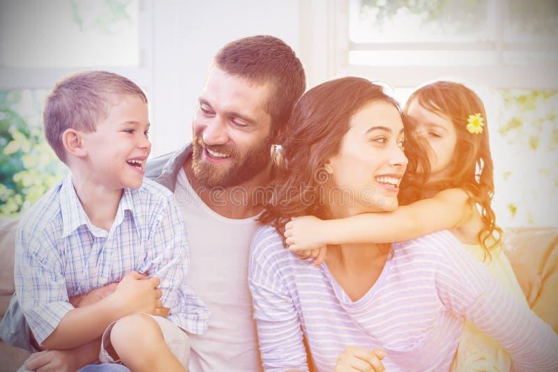 Föräldrar och ungar som har gyckel, medan sitta på soffan royaltyfri fotografi