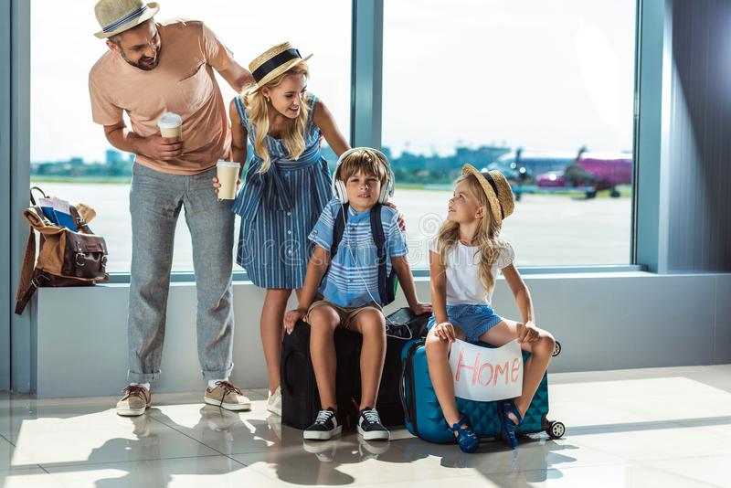Föräldrar och ungar som väntar på logi i flygplats arkivbilder