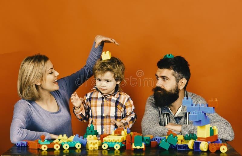 Föräldrar och unge i lekrum Dagis- och familjbegrepp Mannen med skägget, kvinnan och pojken spelar på röd bakgrund royaltyfri fotografi