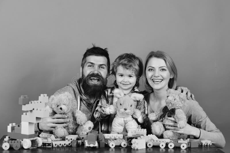 Föräldrar och unge i lekrum Familjen med lyckliga framsidor rymmer kvarter för konstruktion för nallebjörnar nära färgade Dagis o royaltyfria foton
