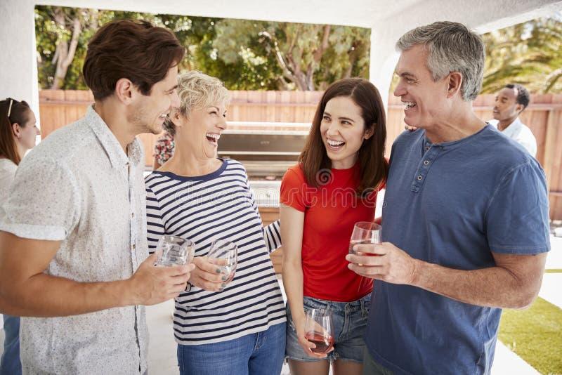 Föräldrar och vuxna barn som står med drinkar i trädgård arkivfoton